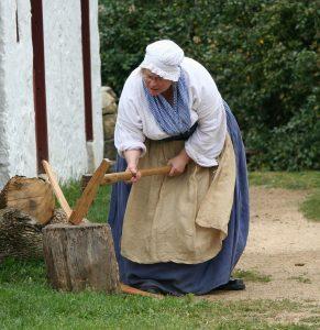 woman splitting wood with an axe